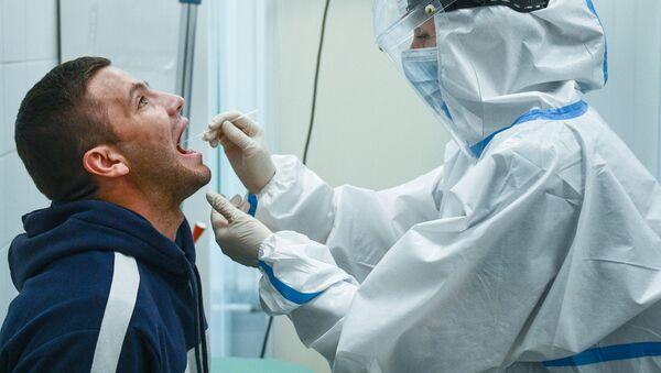 El personal médico recoge el material biológico para hacer una prueba de COVID-19 - Sputnik Mundo