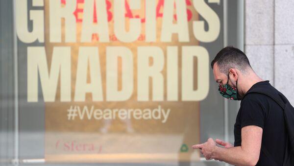Un hombre pasa junto a una tienda que tiene un mensaje que dice Gracias Madrid. Foto de archivo.  - Sputnik Mundo