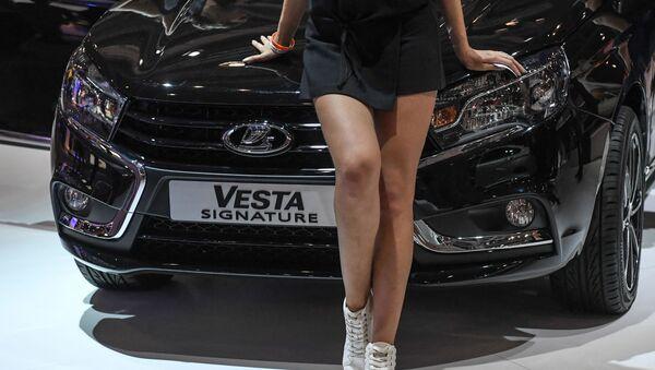Una modelo posa delante de un Lada Vesta en el Salón del Automóvil de Moscú de 2016 - Sputnik Mundo