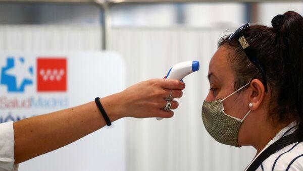 Una mujer tomando temperatura durante rebrote de coronavirus en España - Sputnik Mundo