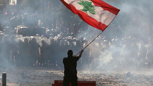 Un manifestante sostiene la bandera del Líbano durante las multitudinarias protestas contra la gestión del Gobierno tras la explosión en el puerto de Beirut, el 8 de agosto de 2020 - Sputnik Mundo
