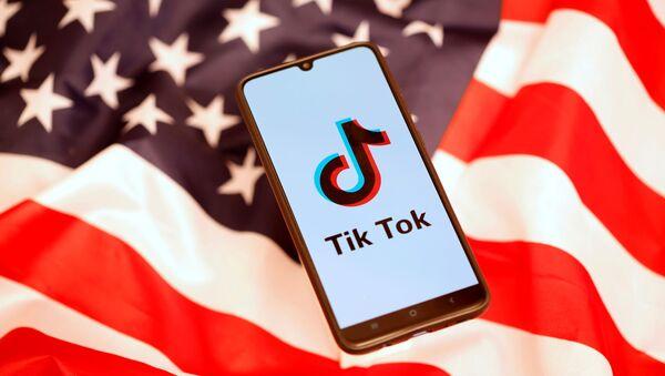 Un 'smartphone' con el logo de TikTok en la pantalla encima de una bandera estadounidense - Sputnik Mundo