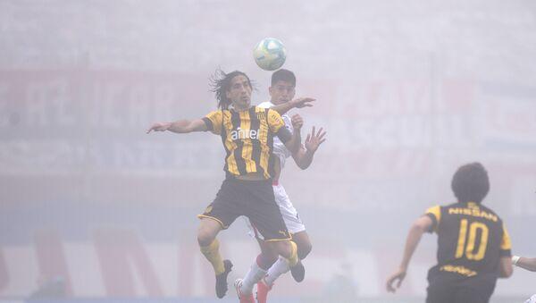Futbolistas de Peñarol y Nacional disputan el balón en el clásico del fútbol uruguayo en medio de una intensa niebla - Sputnik Mundo