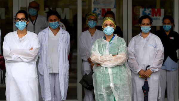 Los trabajadores sanitarios guardan un minuto de silencio para rendir homenaje a sus compañeros caídos frente al Hospital Gregorio Marañón - Sputnik Mundo