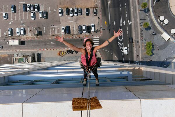 Специалист по мойке окон Ноа Толедо во время работы на высотном здании в Тель-Авиве, Израиль - Sputnik Mundo