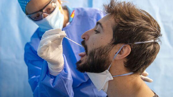 Un trabajador de la salud toma una muestra para una prueba de PCR para el COVID-19 en un centro médico en Madrid. 17 de agosto - Sputnik Mundo