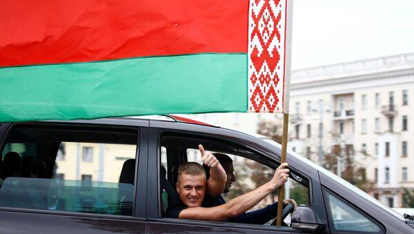 Un hombre ondea la bandera nacional bielorrusa desde la ventana de un automóvil en Minsk, Bielorrusia - Sputnik Mundo