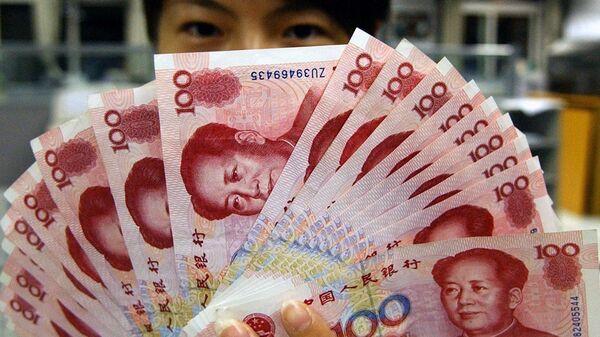 Una mujer sostiene yuanes - Sputnik Mundo