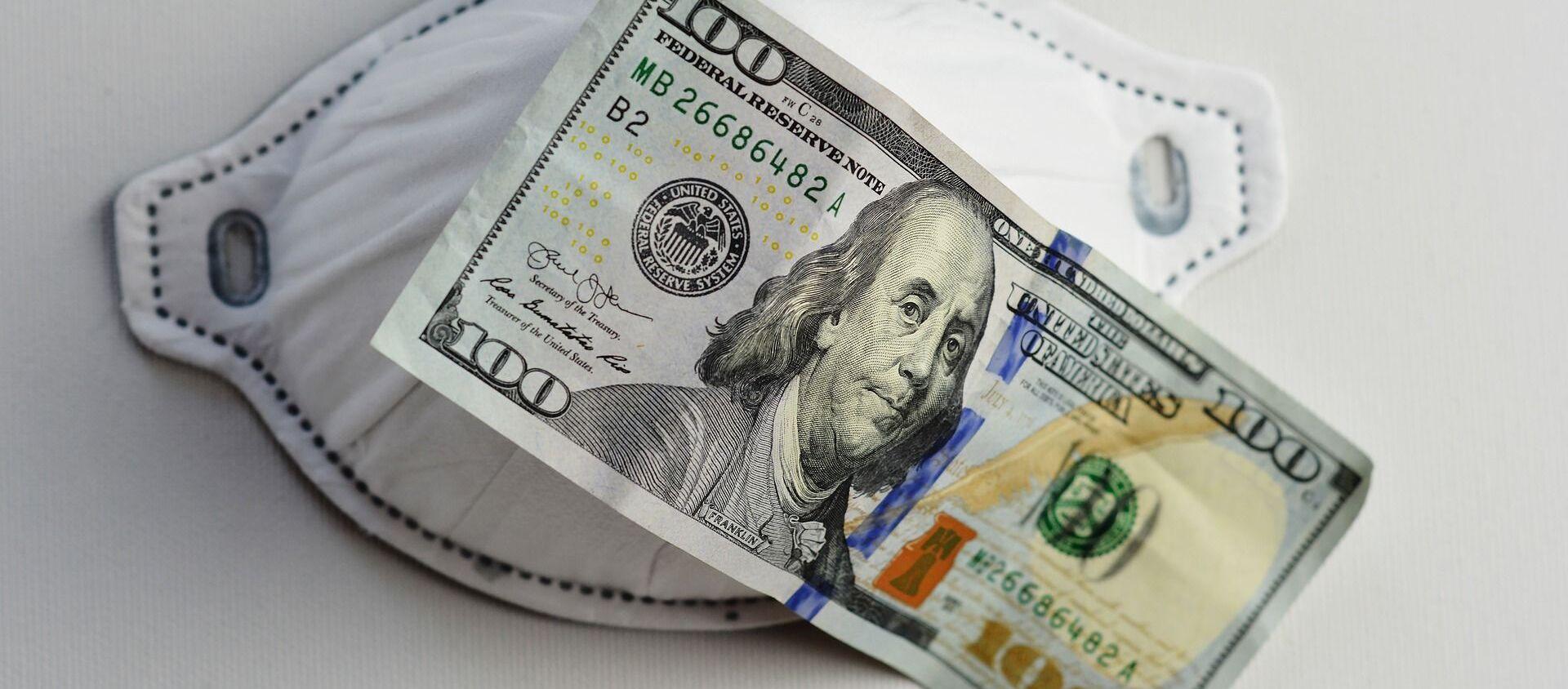 Una mascarilla y un billete de 100 dólares - Sputnik Mundo, 1920, 04.02.2021