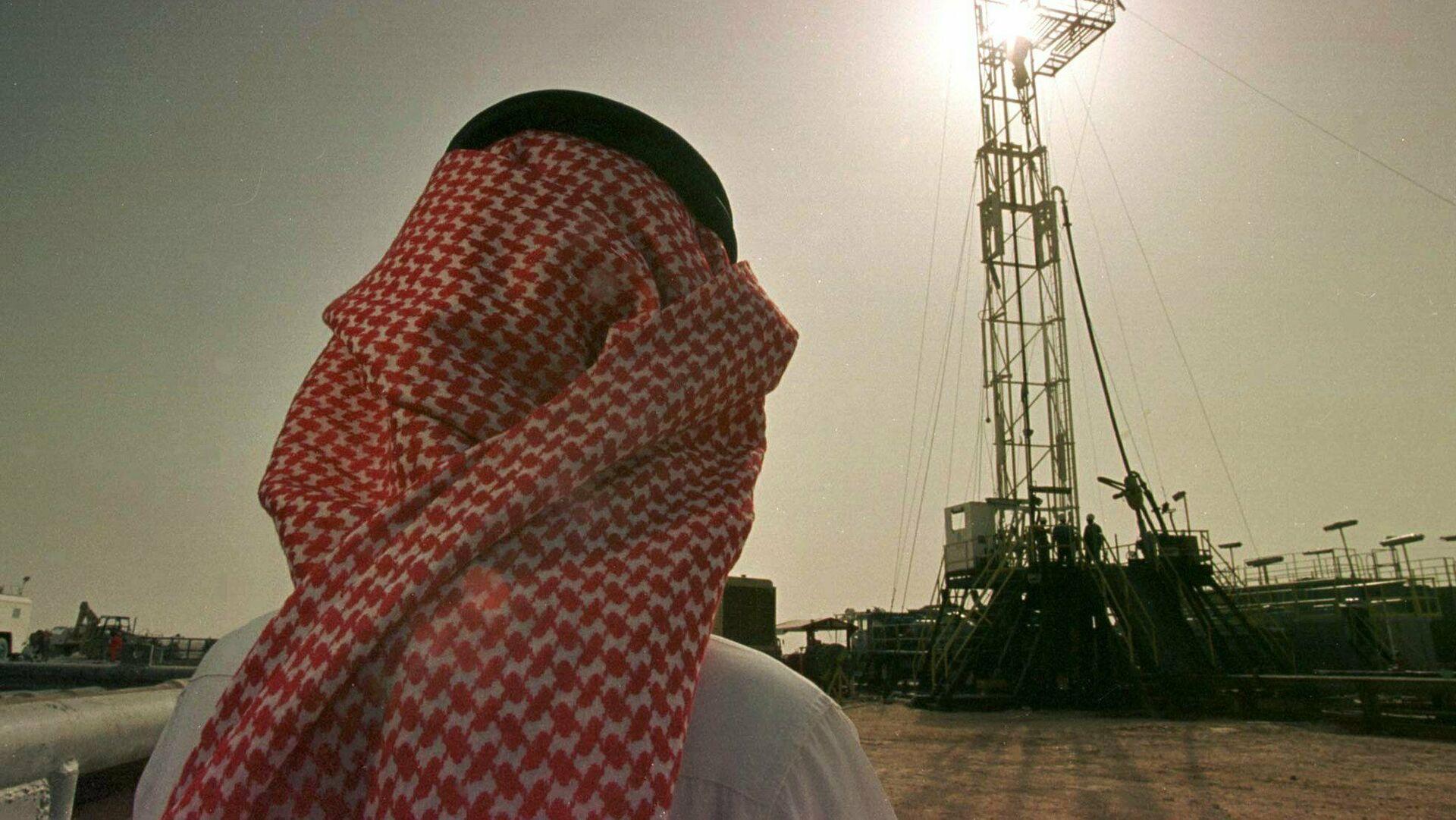 Un empleado de la compañía petrolera saudí Aramco observa el progreso de una plataforma situada en un yacimiento petrolero  - Sputnik Mundo, 1920, 26.03.2021