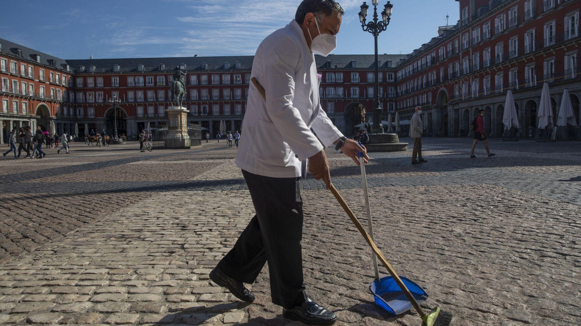 Un camarero con mascarilla limpiando en una de las terrazas de la Plaza Mayor de Madrid - Sputnik Mundo, 1920, 01.02.2021