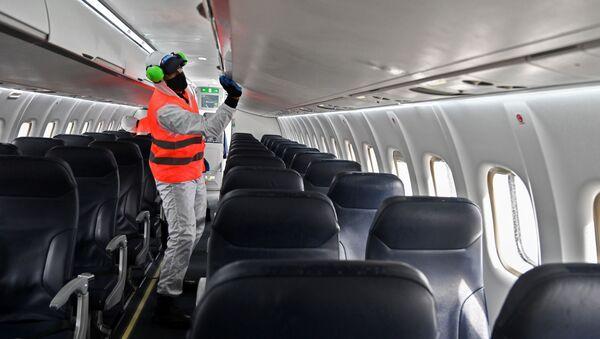 Imagen referencial de medidas de higiene por el COVID-19 en el interior de un avión - Sputnik Mundo
