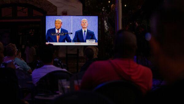 Unas personas siguen el último debate entre los candidatos Joe Biden y Donald Trump antes de las elecciones presidenciales de EEUU - Sputnik Mundo