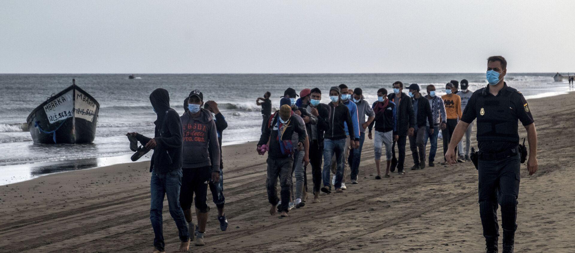 Migrantes de Marruecos caminan por la orilla escoltados por la Policía española tras llegar a la costa de Canarias - Sputnik Mundo, 1920, 19.01.2021
