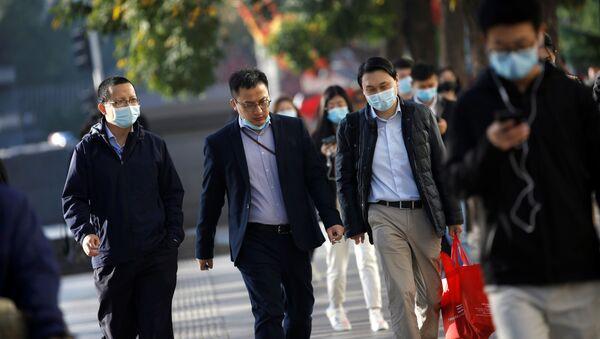 Una personas con mascarillas caminan por las calles de Pekín - Sputnik Mundo