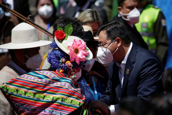 Al momento de arribar a su acto de investidura, Luis Arce saluda a una mujer de las organizaciones sociales que se encontraban en medio de la multitud para presenciar la toma de posesión - Sputnik Mundo