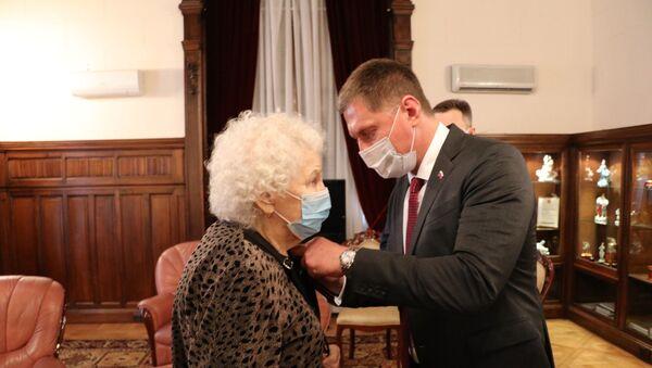 El embajador de Rusia en Argentina, Dmitri Feoktístov, condecorando a una veterana de la Gran Guerra Patria residente en Argentina - Sputnik Mundo
