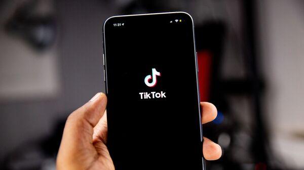 Una persona sostiene un teléfono en el que se ve el logo de TikTok - Sputnik Mundo