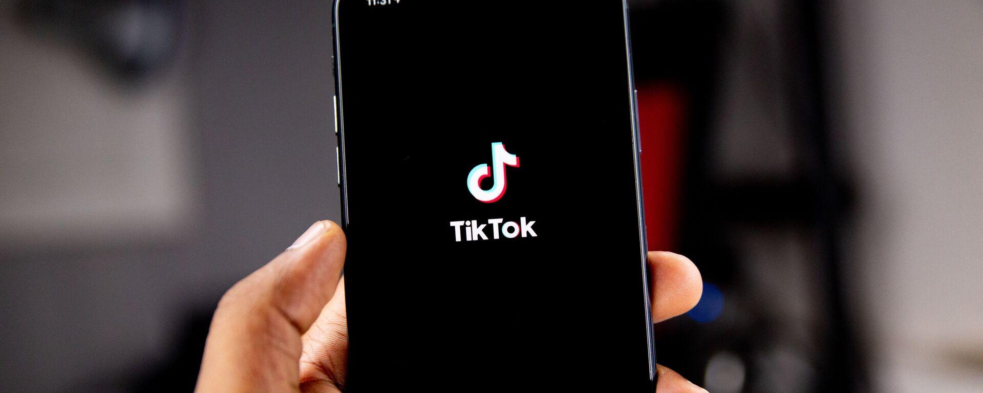 Una persona sostiene un teléfono en el que se ve el logo de TikTok - Sputnik Mundo, 1920, 27.01.2021