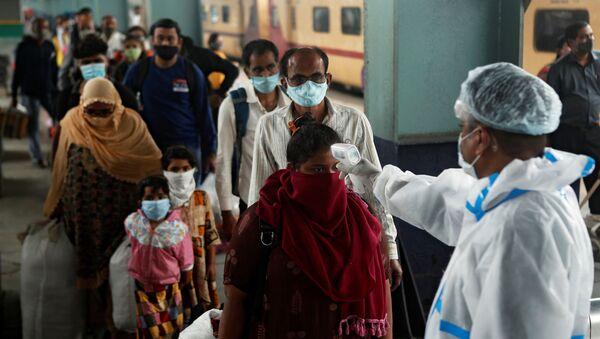 Un trabajador de la salud revisa la temperatura de los pasajeros en una estación de tren de Mumbai, la India. - Sputnik Mundo