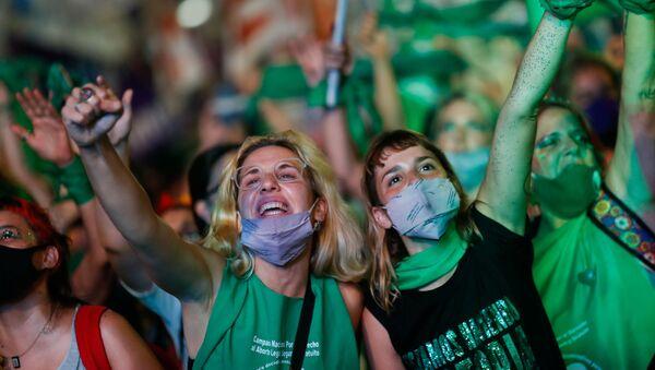Mujeres celebran la aprobación de la ley sobre la interrupción voluntaria del embarazo (IVE), en Buenos Aires (Argentina), el 30 de diciembre del 2020 - Sputnik Mundo