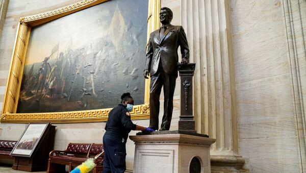Una empleada del Capitolio limpia una estatua del expresidente Ronald Reagan ubicada en el interior de la Rotonda del Capitolio - Sputnik Mundo