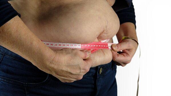 Una persona se mide la barriga con una cinta métrica - Sputnik Mundo