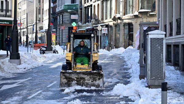Un operario quita la nieve de la calzada en una céntrica calle de Madrid - Sputnik Mundo
