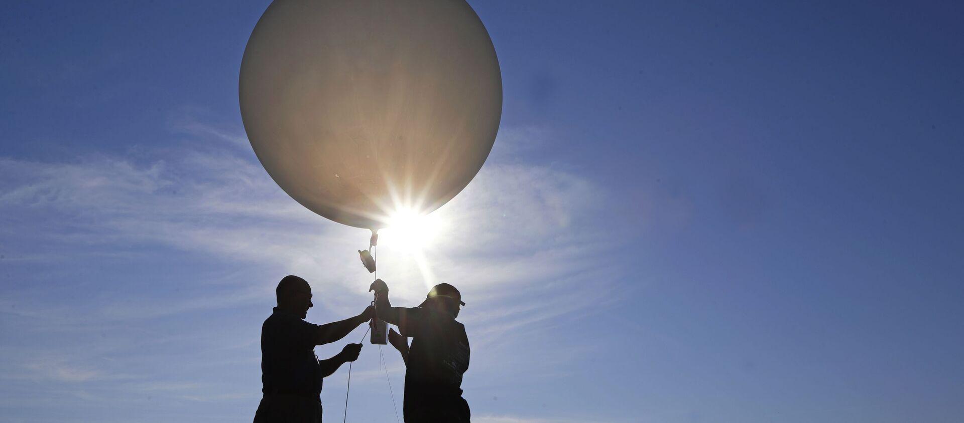 Unas personas lanzan un globo meteorológico (imagen referencial) - Sputnik Mundo, 1920, 05.02.2021