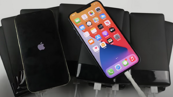 un iPhone 12 Pro Max con un cargador MagSafe y el otro con 10 'powerbanks'  - Sputnik Mundo