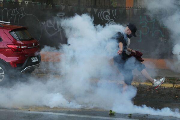 El incidente ocurrió el 5 de febrero. Un vídeo, en el que un uniformado realiza varios disparos contra el malabarista callejero Francisco Martínez luego de que este se negara a seguir sus órdenes, se viralizó en las redes. En la foto: un manifestante empuja una bomba lacrimógena lanzada por la Policía.  - Sputnik Mundo