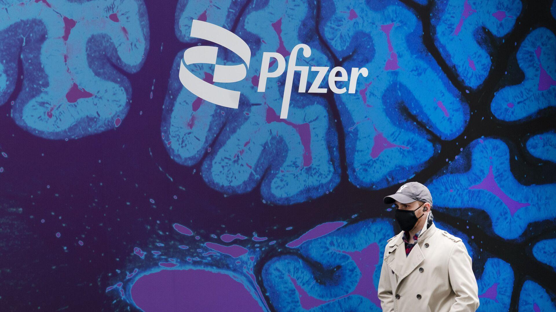 Un hombre camina frente a un logo del laboratorio de Pfizer frente a la sede del laboratorio en Nueva York - Sputnik Mundo, 1920, 19.09.2021