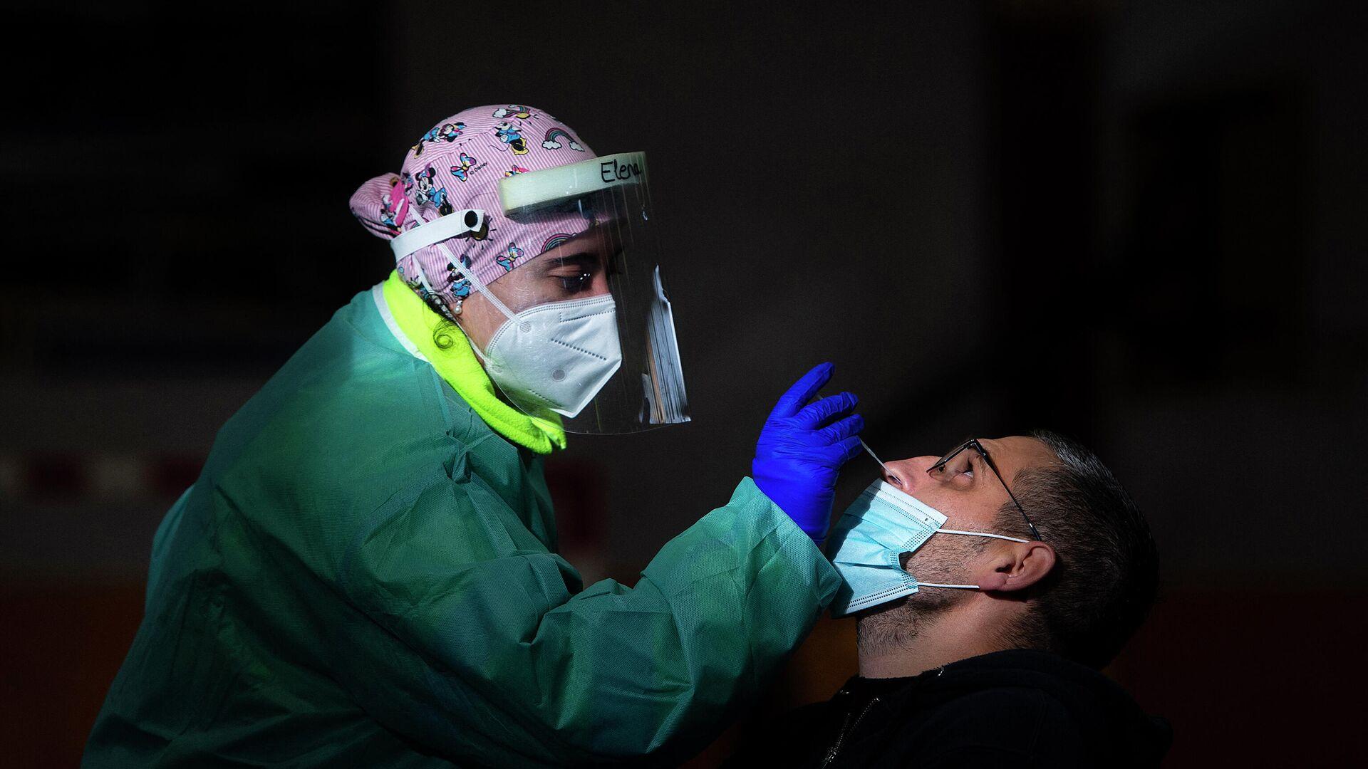 Una trabajadora de la salud realiza una prueba rápida de antígeno para COVID-19 durante una detección masiva de coronavirus en Tui, noroeste de España, el 8 de diciembre de 2020. - Sputnik Mundo, 1920, 12.03.2021