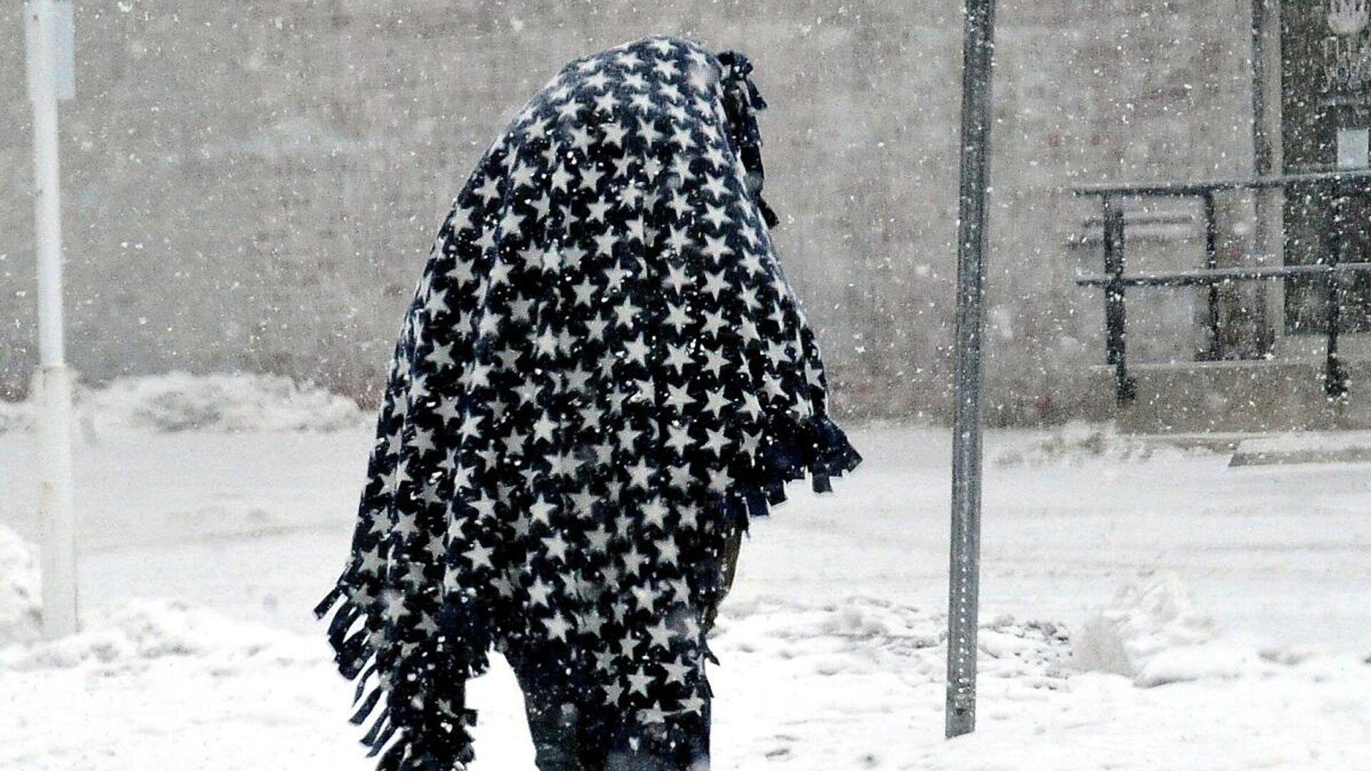 Una persona camina cubierta por una manta para mantenerse caliente después de una tormenta de nieve en el centro comercial de Wooster, Ohio, EEUU, el 15 de febrero de 2021.   - Sputnik Mundo, 1920, 17.02.2021