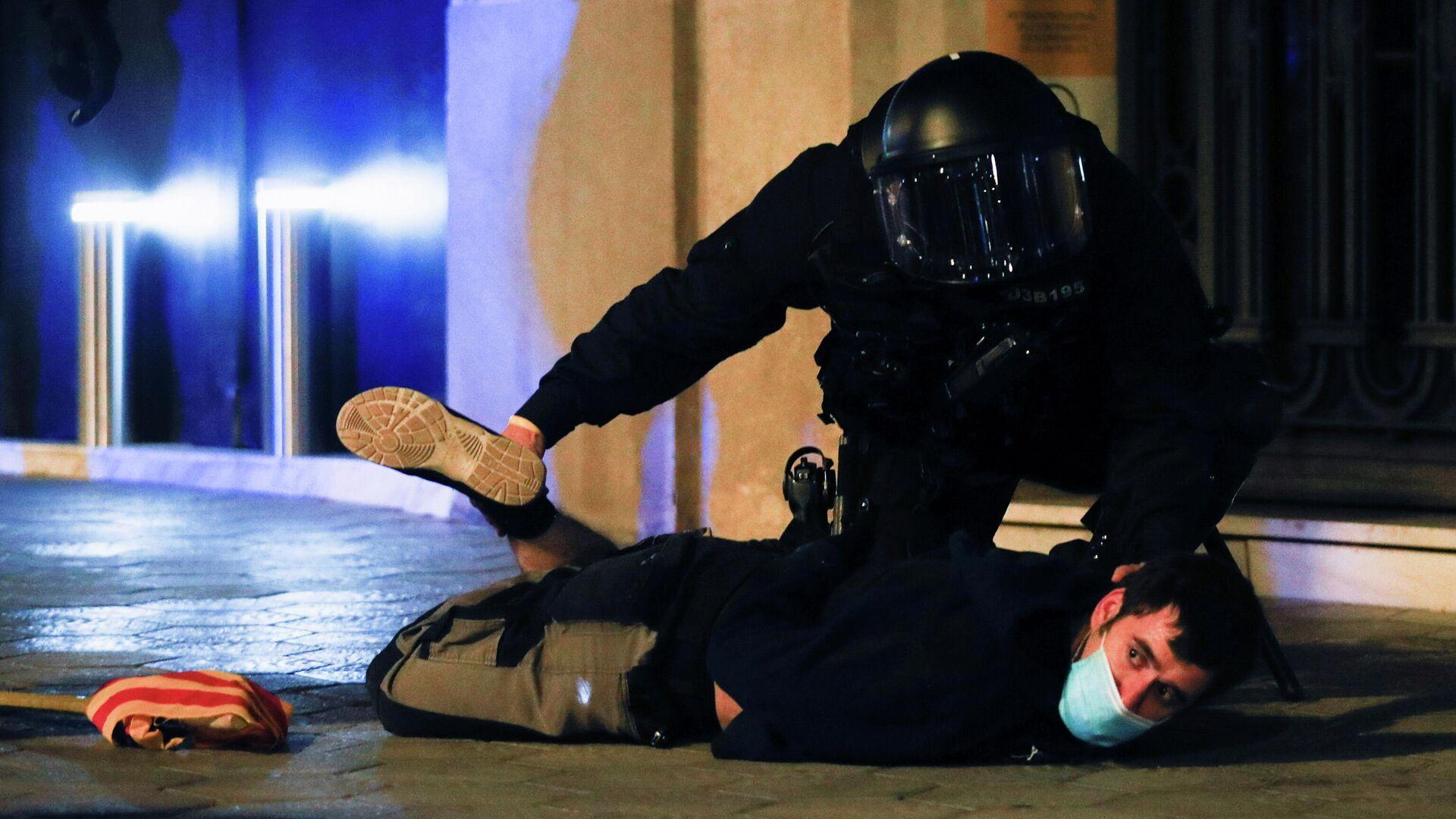 Un policía deteniendo a un manifestante durante los disturbios en Barcelona, España - Sputnik Mundo, 1920, 20.02.2021