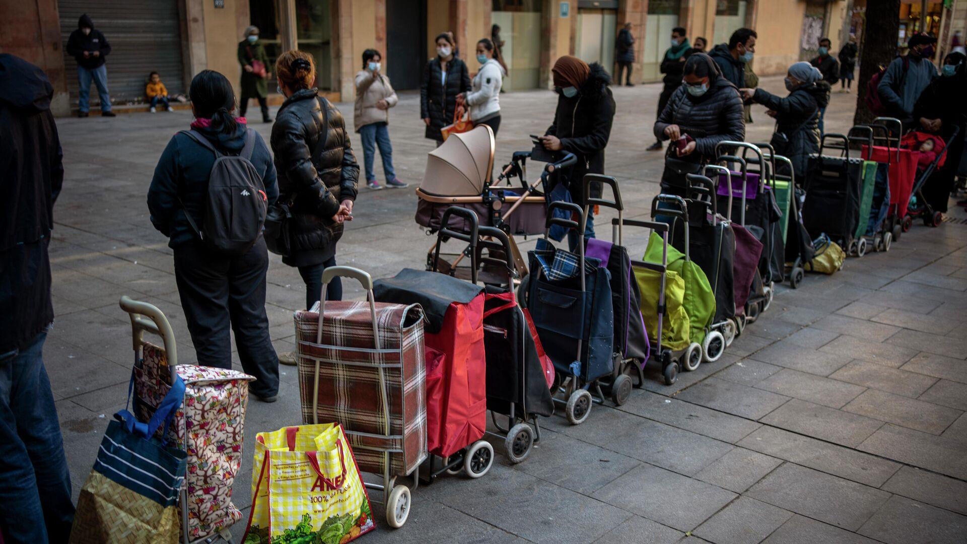 Carritos de compras alineados junto a sus dueños, esperando su turno para recibir un paquete semanal de alimentos y suministros donados, afuera de una iglesia en Barcelona, España, el miércoles 3 de febrero de 2021. - Sputnik Mundo, 1920, 04.03.2021
