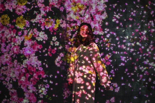 Una joven se hace una foto en la exposición Teamlab Borderless, en la ciudad de Shanghái, China. - Sputnik Mundo