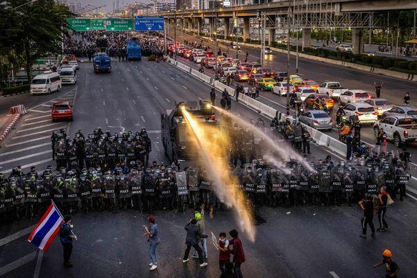 La Policía en la ciudad de Bangkok usa cañones de agua para dispersar a los manifestantes que se dirigen hacia la residencia del primer ministro de Tailandia, Prayut Chan-O-Cha. - Sputnik Mundo