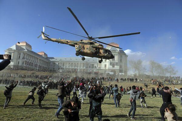 Un helicóptero militar vuela sobre los visitantes de la exposición Afghan Security Forces Exhibition que se celebra en el territorio del Palacio Darul Aman en la ciudad de Kabul. - Sputnik Mundo