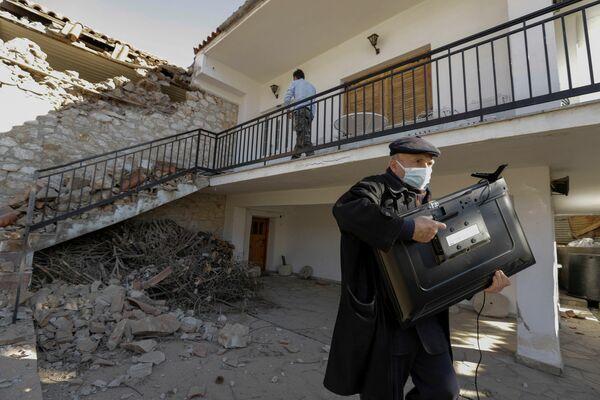 Un hombre lleva un televisor que se quedó intacto de su casa destruida por un terremoto en el pueblo de Damasi en Grecia Central. - Sputnik Mundo
