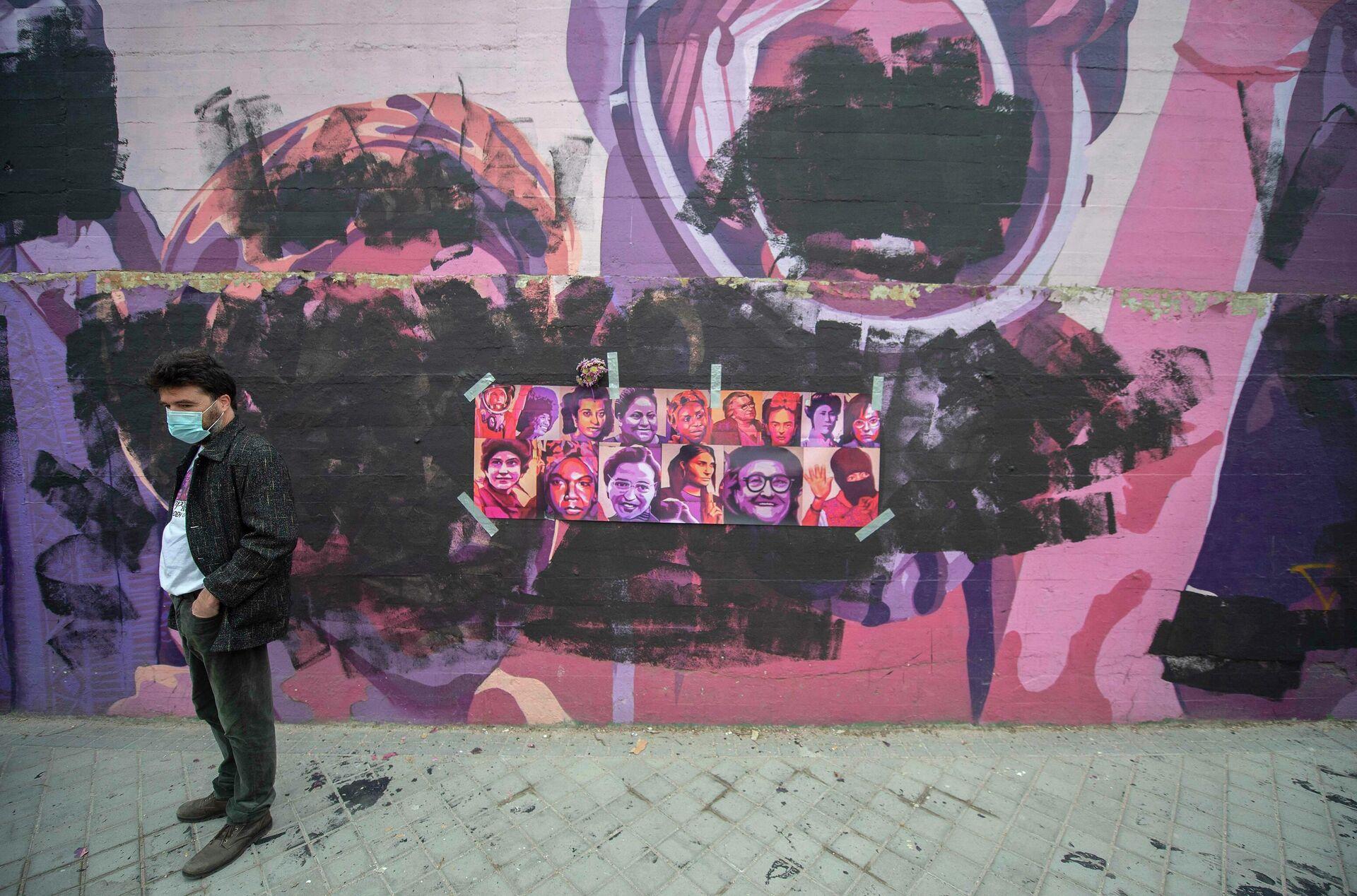 Un hombre pasa al lado del mural feminista que ha sido vandalizado.  - Sputnik Mundo, 1920, 08.03.2021