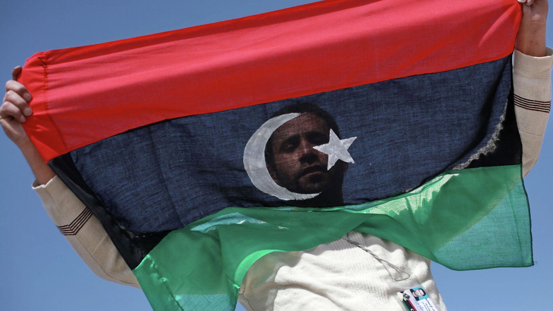 Un opositor con la bandera de Libia - Sputnik Mundo, 1920, 21.09.2021