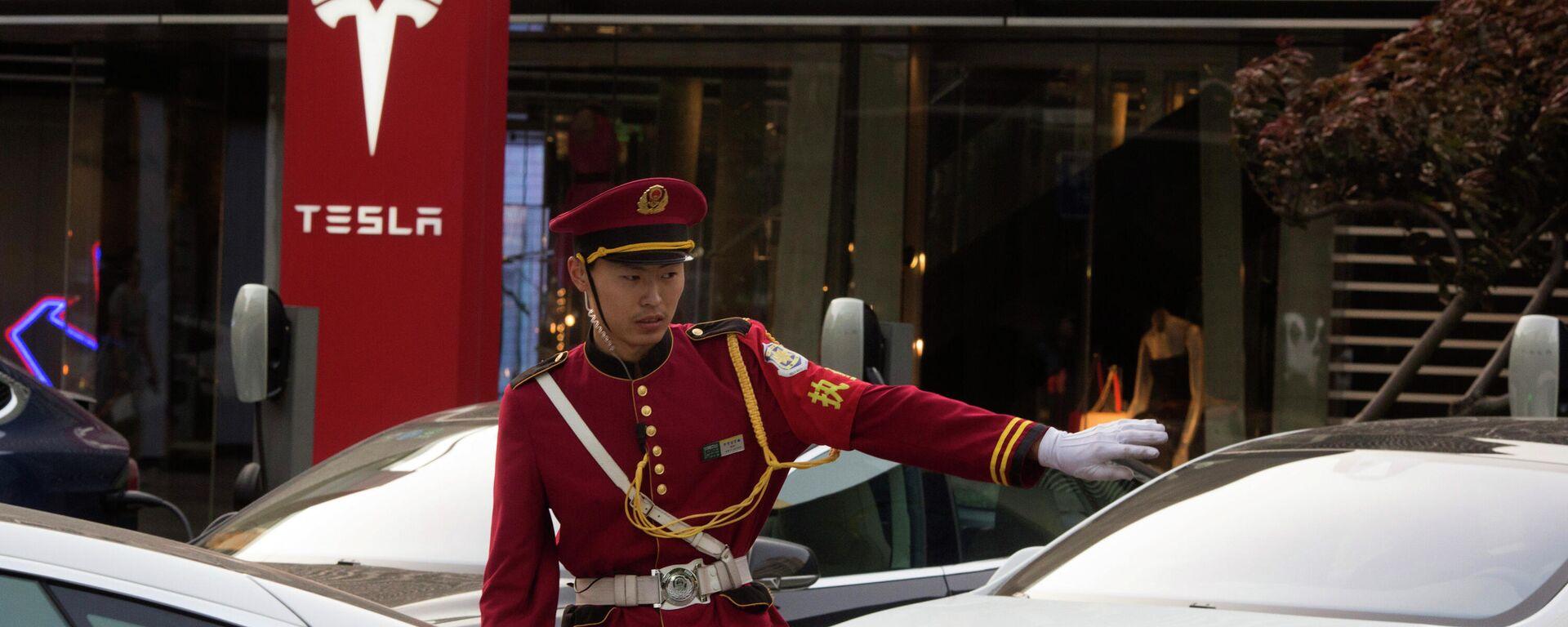 Un guardia de seguridad dirige el tráfico cerca de una estación de carga de Tesla en Pekín, China. - Sputnik Mundo, 1920, 20.03.2021