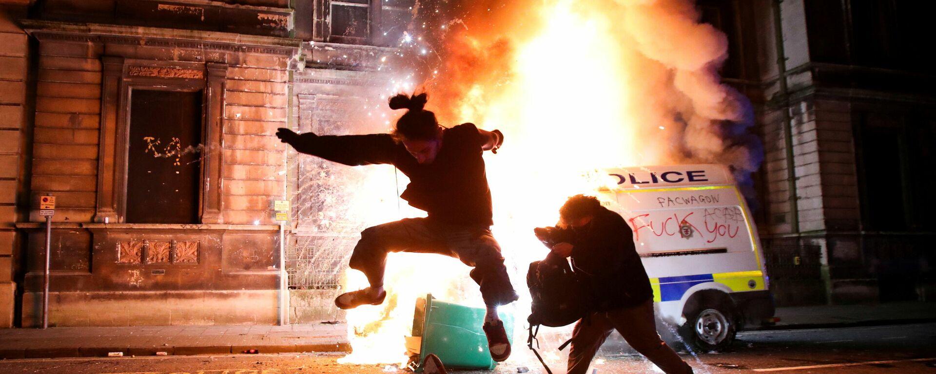 Демонстрант катается на скейтборде перед горящей полицейской машиной во время акции протеста в Бристоле, Великобритания - Sputnik Mundo, 1920, 28.03.2021