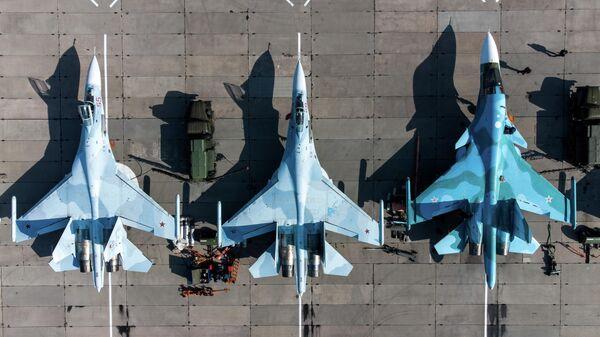 Unos cazas multipropósito Su-35S (a la izquierda) y cazabombardero SU-34 (a la derecha) de las Fuerzas Aeroespaciales de Rusia - Sputnik Mundo
