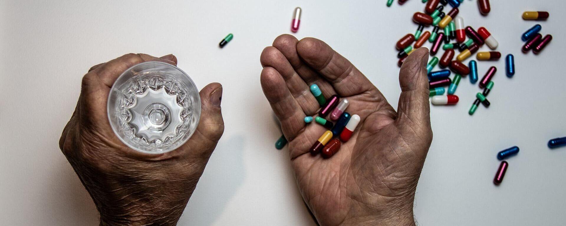 Una persona a punto de tomar píldoras - Sputnik Mundo, 1920, 24.07.2021