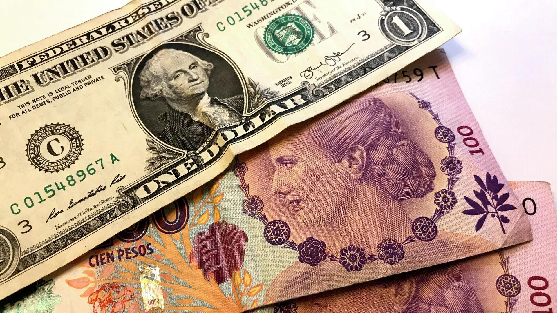 Pesos argentinos y un billete de dólar - Sputnik Mundo, 1920, 19.08.2021