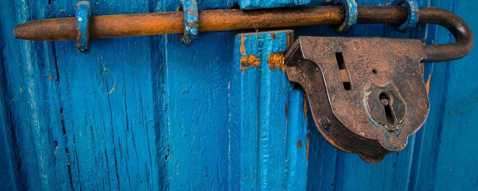 Una puerta cerrada con candado. Imagen referencial - Sputnik Mundo, 1920, 02.06.2021