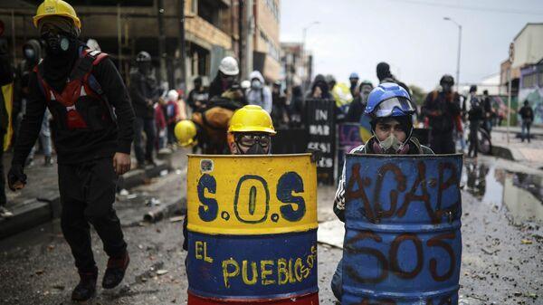 Антиправительственные протестующие прячутся за импровизированными щитами во время столкновений с полицией в Боготе, Колумбия - Sputnik Mundo