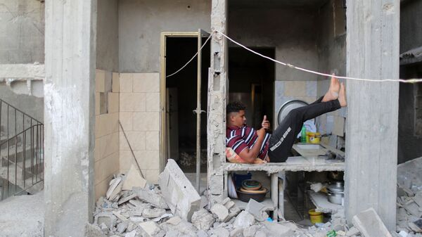Палестинец в разрушенном здании в Газе - Sputnik Mundo